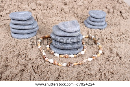 large flat stones lie in the shape of a pyramid on the sand - stock photo