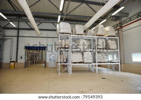 Large food warehouse with steel shelves ans sugar sacks - stock photo