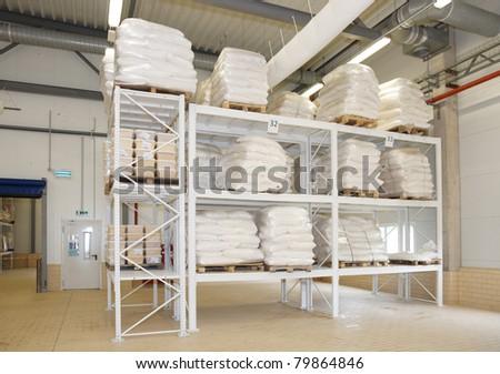 Large food warehouse with sugar sacks on steel shelves - stock photo
