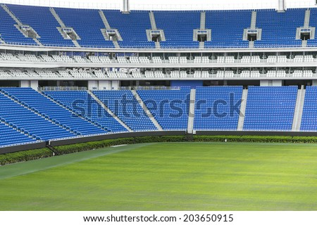 Large football stadium with green grass and blue seats - stock photo