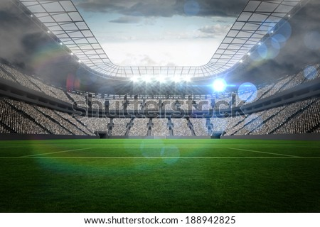 Large football stadium with lights under cloudy sky - stock photo