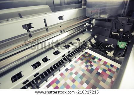 large format ink jet printer printing color management target on paper roll, VINTAGE - stock photo