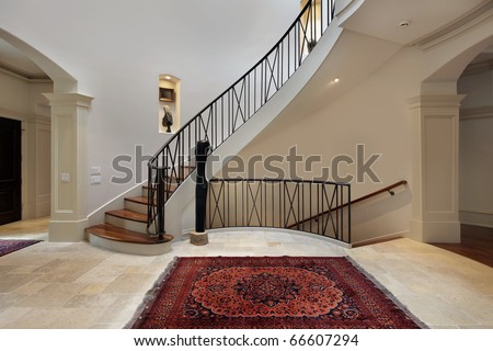 Large foyer in luxury home with circular staircase - stock photo