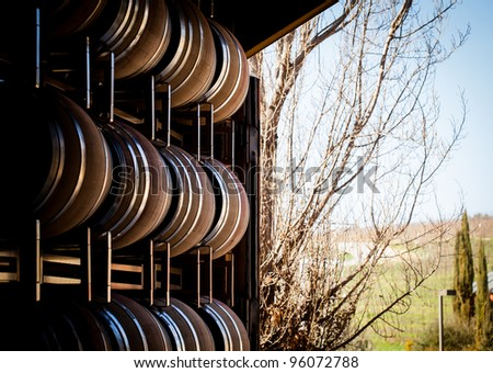 Large French Oak Wine Barrels stacked near a roll up door at a winery in paso robles - stock photo