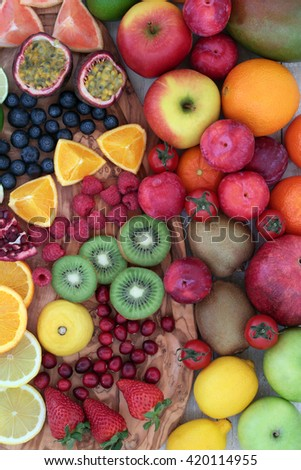 Large fresh fruit background on an olive wood board. High in antioxidants, anthocyanins, dietary fiber and vitamins. - stock photo