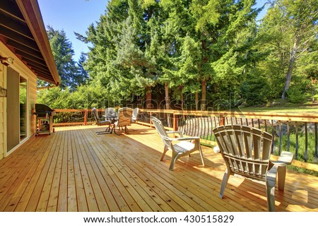 Large freshly painted new wooden deck with nice summer green backyard and outdoor furniture. - stock photo