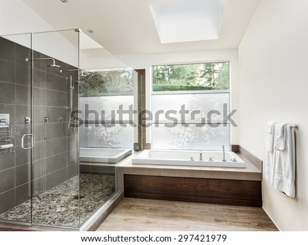 Large furnished bathroom in luxury home with hardwood floor, shower, and bathtub - stock photo