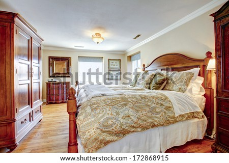 Large furnished bedroom with rustic furniture and hardwood floor - stock photo