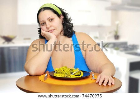 Large girl eating a measuring tape - stock photo