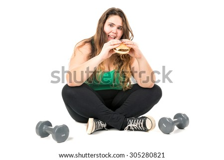 Large girl seated with dumbbells eating a hamburger isolated in white - stock photo