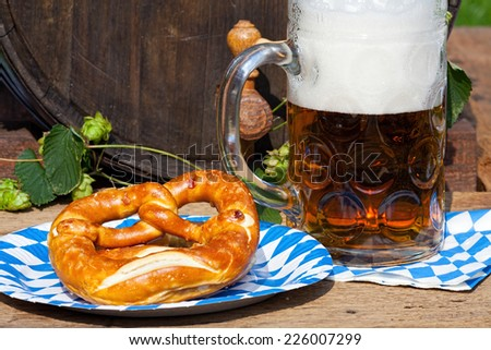 Large glass of beer and pretzel on a paper plate