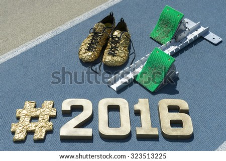 Large gold hashtag 2016 message with matching shoes next to starting blocks on a textured blue and tan running track - stock photo
