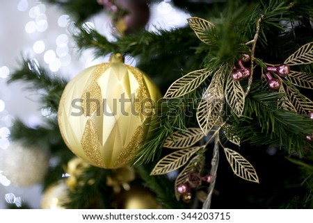 Large golden ball hanging on a Christmas tree green pine branch with small thorny needles. Beautiful garlands and decorations for festive party mood. Horizontal photo card for the New Year Greetings. - stock photo