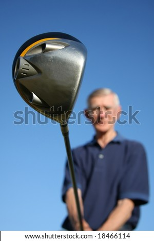 Large golf club with out of focus man in the background - stock photo