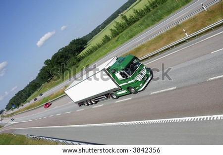 large green white truck speeding on highway, green forrest and fields in background - stock photo
