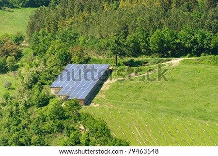 large greenhouse covered with solar panels on the hills of Italy in Predappio - stock photo