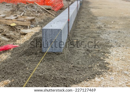 Large grey granite curb stone and string with stakes to level at road construction site. Selective focus. - stock photo