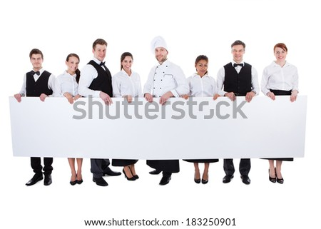 Large group of catering staff holding a blank banner with copyspace for your text including a chef  waiters  waitresses  hostess and wine steward  isolated on white