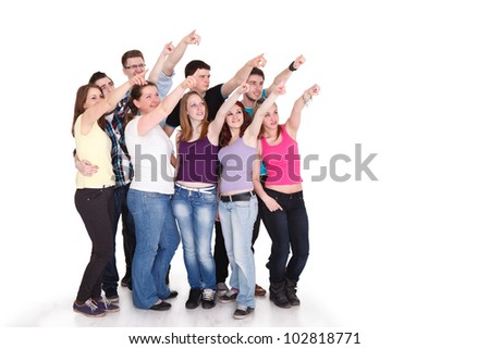 Large group of cheerful students pointing at copy space on white background - stock photo
