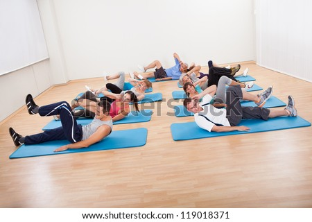 Large group of diverse people exercising in a gym class lying on blue mats doing leg raising and twisting exercises - stock photo