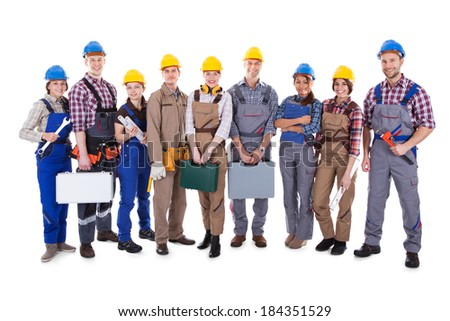 Large group of diverse workmen and women standing in a row holding their tools and equipment and wearing hardhats  isolated on white - stock photo