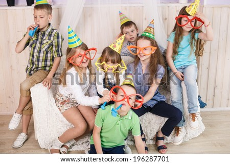 Large group of diversity looking kids, boys and girls sitting on the couch at home, hugging, smiling and laughing - stock photo