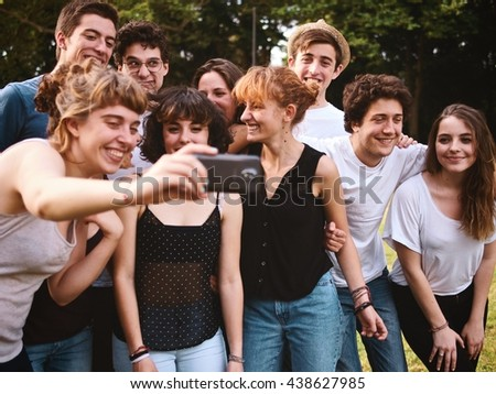 large group of friends together in a park having fun taking selfie with a smartphone