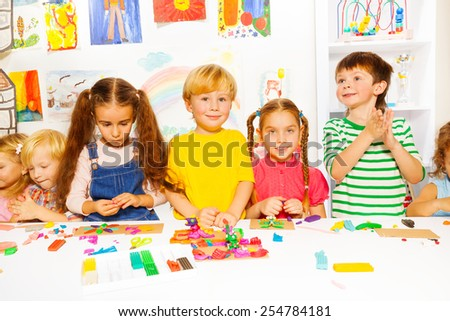 Large group of happy diverse looking preschool kids boys and girls play with plasticine on a lesson - stock photo