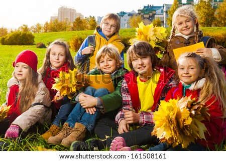 Large group of kids, boys and girls sitting in the grass in autumn clothes with maple leaves bouquets and papers after school - stock photo