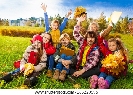 Large group of kids, friends, boys and girls around 10 years old, sitting in the grass in autumn clothes with maple leaves bouquets and papers after school with lifted hands - stock photo