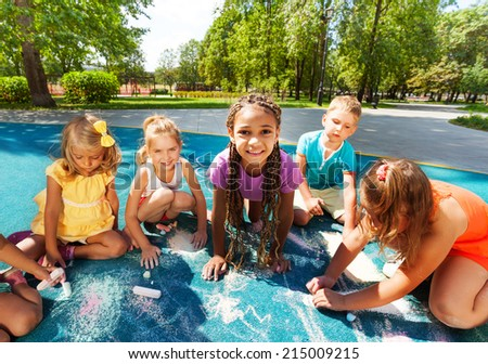 Large group of little kids draw with chalk - stock photo