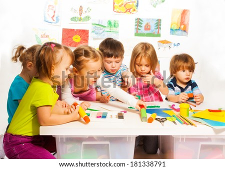 Large group of little kids on painting class sitting together with pencils and paints - stock photo