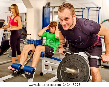 Large group of men and women working his body  at gym. He lifting barbell and abs training. - stock photo