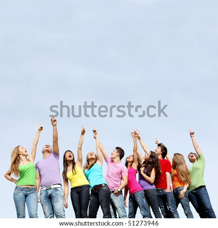 large group of mixed race kids pointing to blank space - stock photo