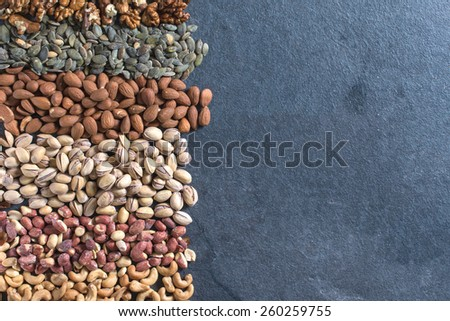 Large group of nuts fruit on dark background with blank space - stock photo