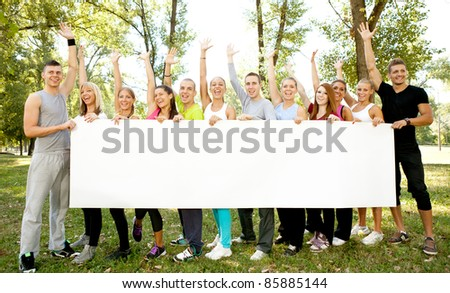 large group of people holding big white paper for advertisements, they are standing in the nature with their arms up and looking at the camera - stock photo