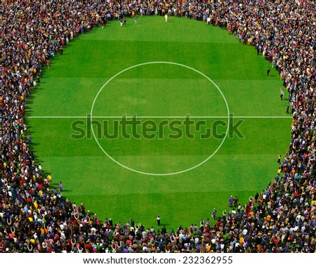 Large group of people seen from above, gathered around a circle, standing on football field background - stock photo