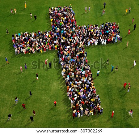 Large group of people seen from above gathered together in the shape of  a cross, on a grass background - stock photo