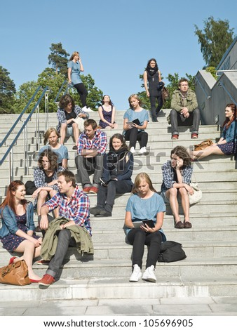 Large group of people sitting in the stairs - stock photo