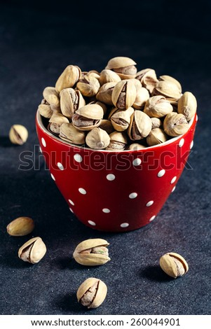 Large group of pistachios in the dotted coffee cup,selective focus  - stock photo