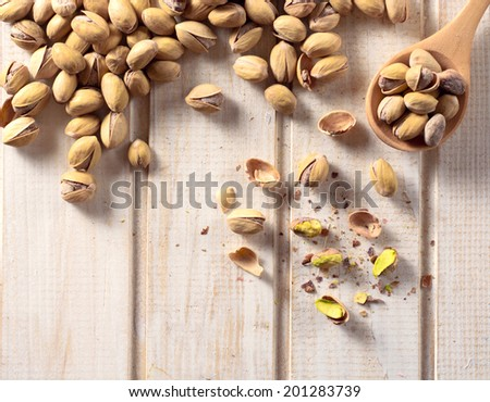 Large group of pistachios on the wooden table from above  - stock photo