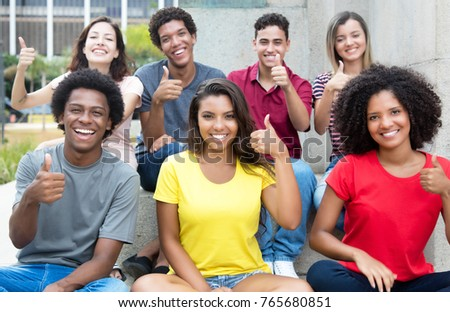 Large group of pretty international young adults showing thumb up