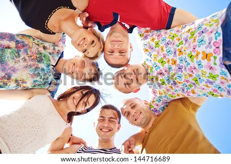Large group of smiling friends staying together and looking at camera isolated on blue background