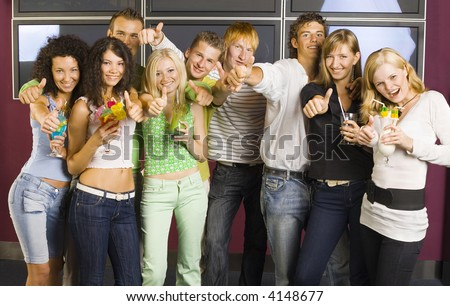 Large group of teenagers during the party. Looking at camera and smiling. Girls holding drinks. Everybody holding thumbs up - stock photo