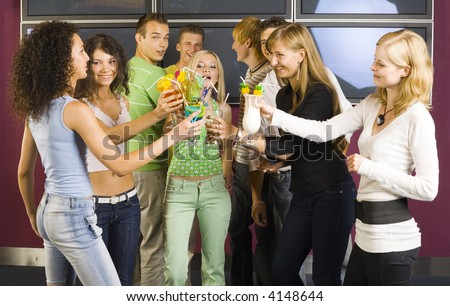 Large group of teenagers during the party. Teenage girls are raising a toast, boys standing behind them and smiling. Two boys are looking at camera - stock photo