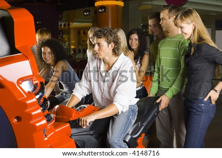 Large group of teenagers in amusement arcade. One teenage boy and girl sitting on motorcycles. Rest of people are standing behind them and smiling - stock photo