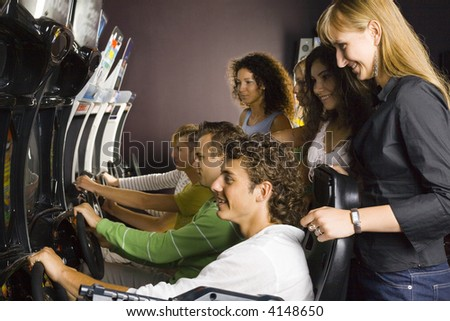 Large group of teenagers in amusement arcade. Teenage girls are standing and smiling, boys driving cars. Side view - stock photo