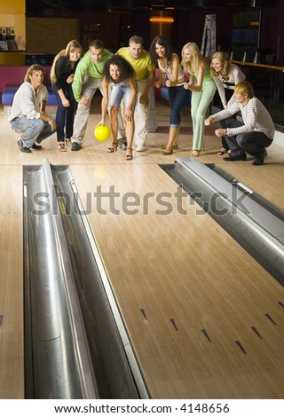 Large group of teenagers standing and crouching in bowling alley. One person is holding ball, others are waiting for strike - stock photo