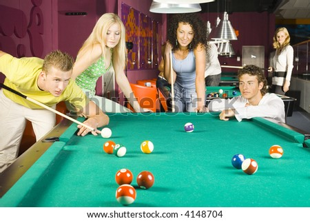 Large group of teenagers standing at pool tables. Smiling and playing billard. One person is very concentrated - stock photo