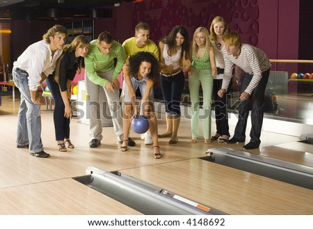 Large group of teenagers standing in bowling alley. One person is holding ball, others are waiting for strike - stock photo